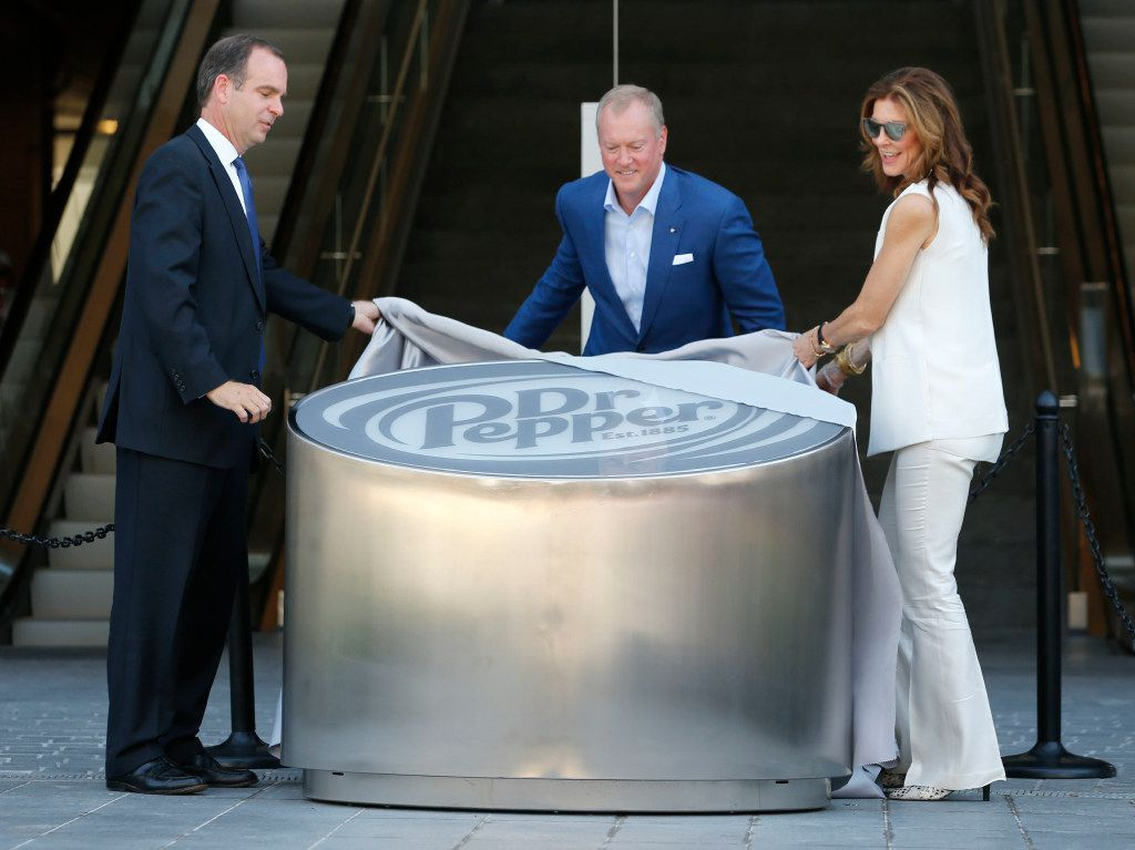 Dr Pepper's senior vice president and chief marketing officer Andrew Springate (left) along with Dallas Cowboys executive vice president Jerry Jones Jr. and Dallas Cowboys executive vice president Charlotte Jones Anderson unveil a Dr Pepper monument during the Ring of Honor Walk ceremony at The Star in Frisco on Aug. 21, 2017.