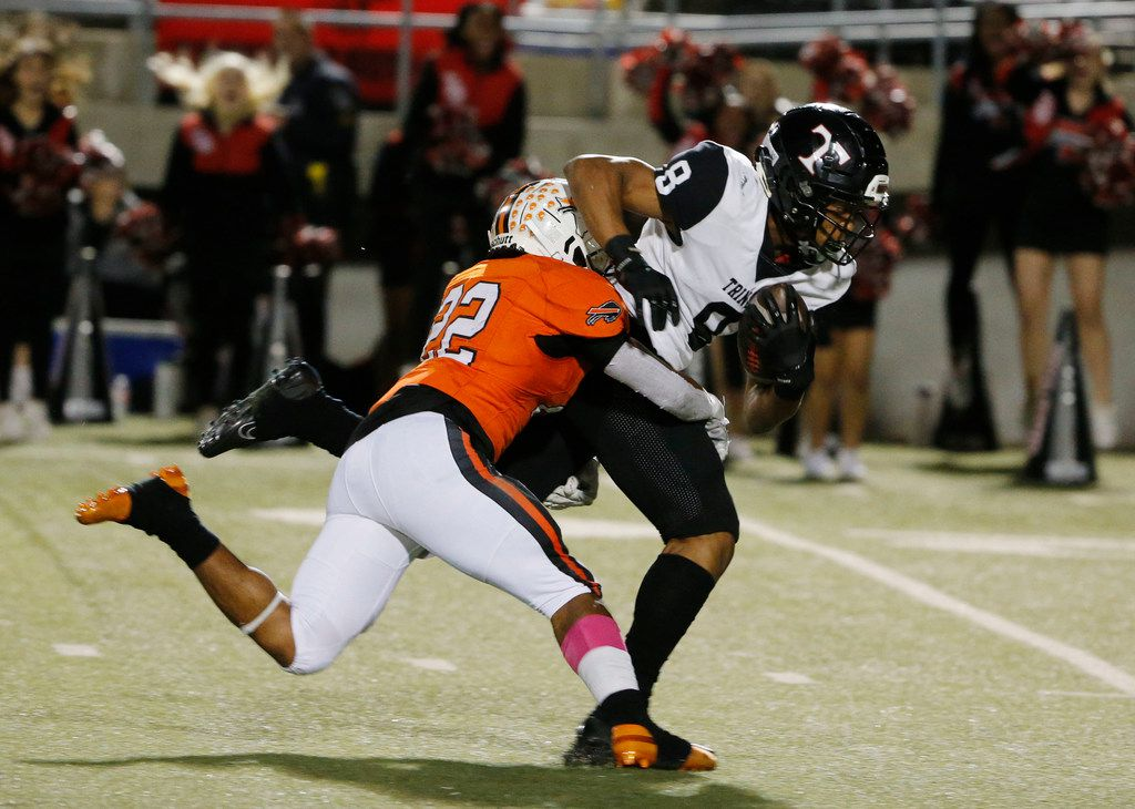 Trinity receiver Camryn Hardy (8) makes a catch and is tackled by Haltom's Johnny Smith-Rider (22) during the first half of their high school football game on Oct. 11, 2019 in North Richland Hills. (Michael Ainsworth/Special Contributor)