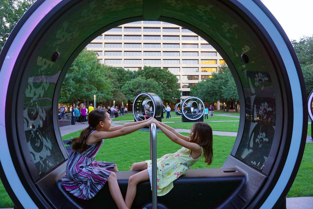 Passersby are welcome to sit inside the cylinders, pump the lever back and forth, and watch a fairy tale story play in and outside of the Loop. (Photo by Nicole Browne)