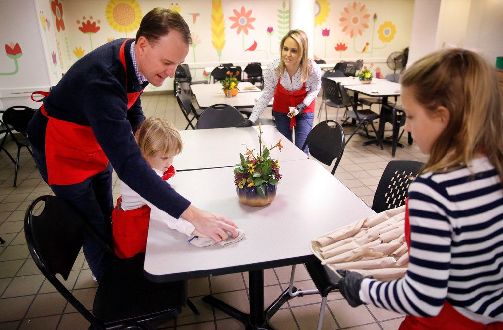 Meredith Land, husband Xan and children Alexander and McCall help set the table for lunch at the Salvation Army's Carr P. Collins Social Service Center on Harry Hines.