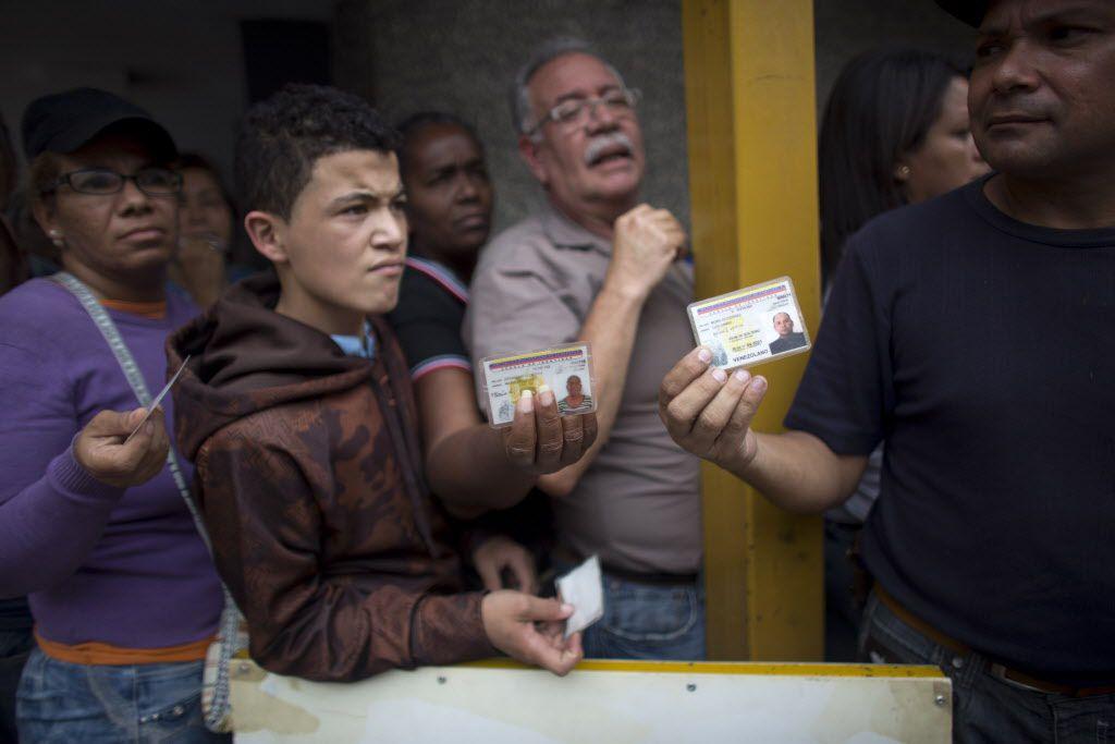 Residentes de Caracas muestran sus credenciales de identificación mientras hacen fila para entrar a un supermercado para comprar comestibles.  (AP/Ariana Cubillos)