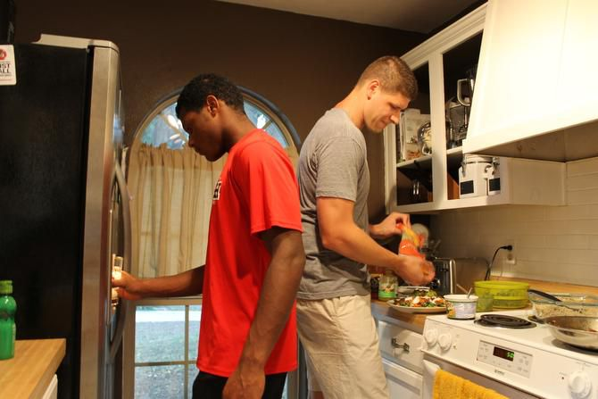 LaQuantis Davis (left) fills his cup with water as Zach Garza puts food on his plate for dinner. A short-term goal of the Forerunner Mentoring Program is to help the mentees not feel alone and to let them know they have a male role model they can trust and count on.