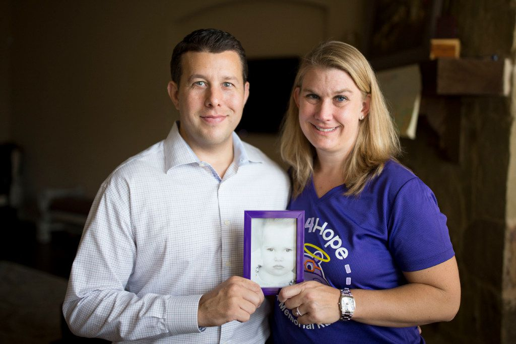 Dustin Howard and Penny Howard pose for a portrait with a photo of their late daughter, Harper, at their home in The Colony. Harper Howard was born with CDKL5, a rare genetic disorder that causes seizures and affects brain development. (Ting Shen/The Dallas Morning News)