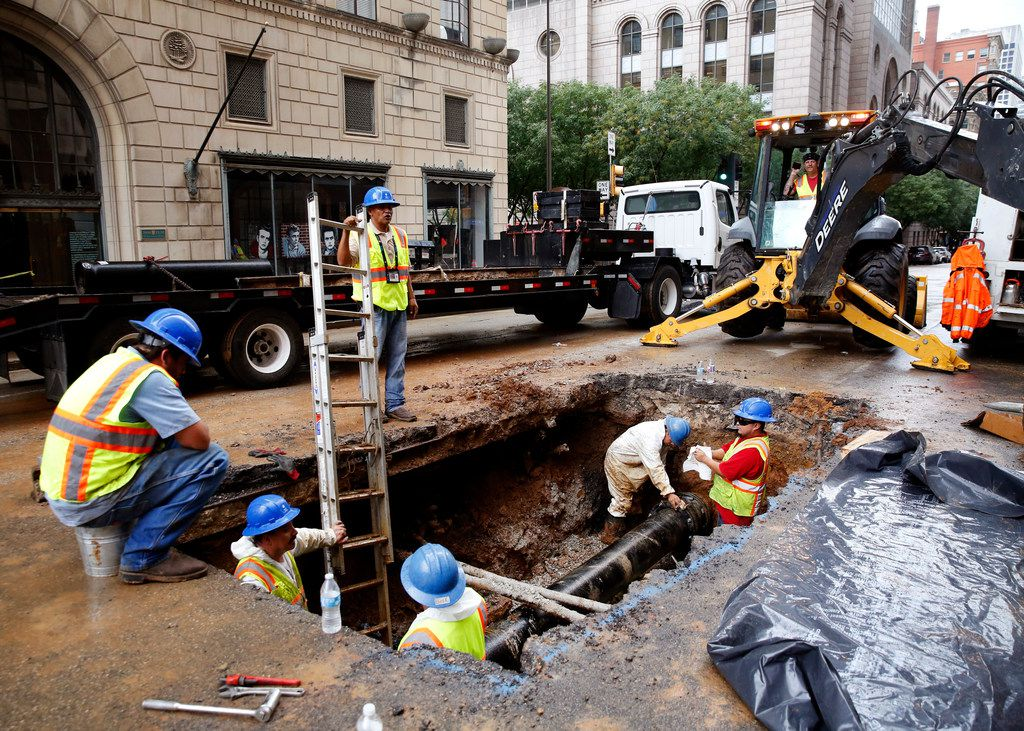 Crews install a new water main at St. Paul and Elm streets in downtown Dallas on Friday, Aug. 10. A broken waterline sent water gushing through downtown Dallas, closed roads and shut down water service in the area.
