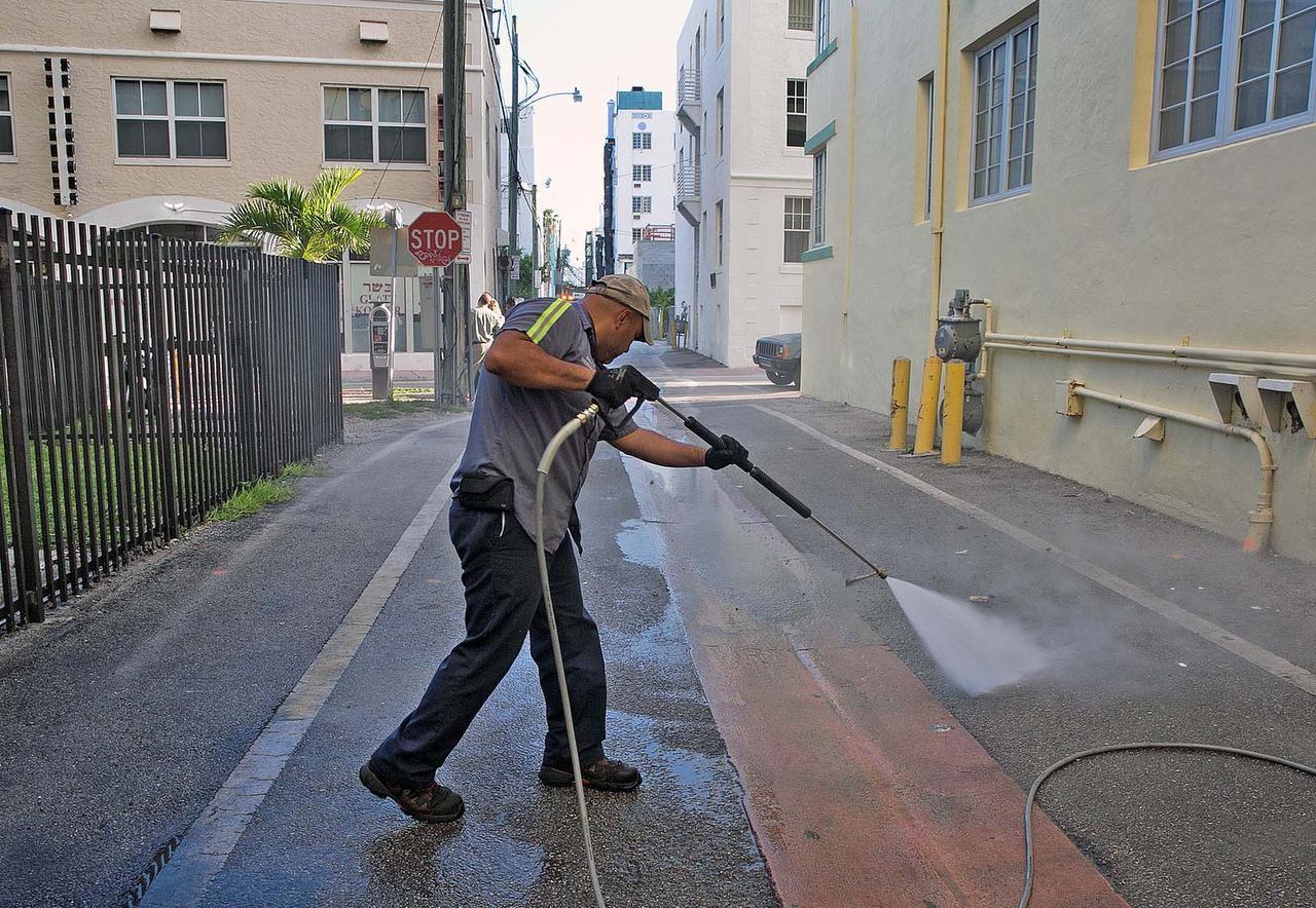 Melvin Gaitán, del Departamento de Salubridad de Miami Beach, limpia un callejón con agua a presión a 250 F para matar larvas de mosquitos. (AP/C.M. GUERRERO)