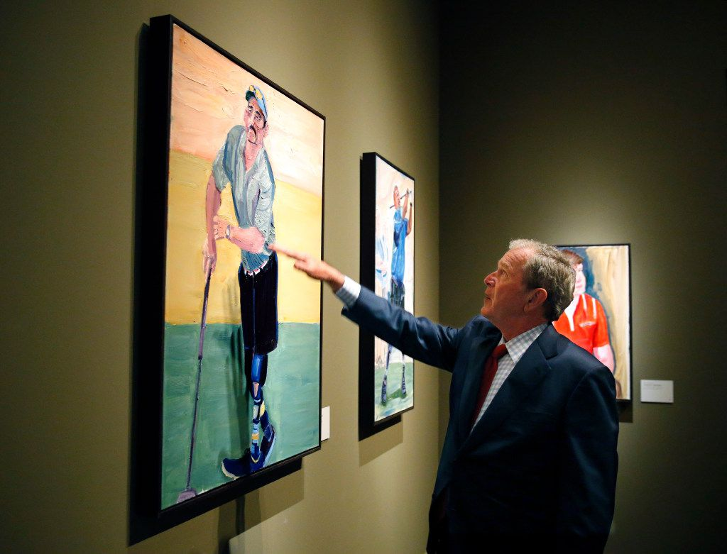 "Former President George W. Bush describes the technique he used to make an oil painting of Sgt. First Class Jacque ""Jake"" Keeslar during a private tour of 'Portraits of Courage, A Commander In Chief 's Tribute To America's Warriors'. (Tom Fox/The Dallas Morning News)"