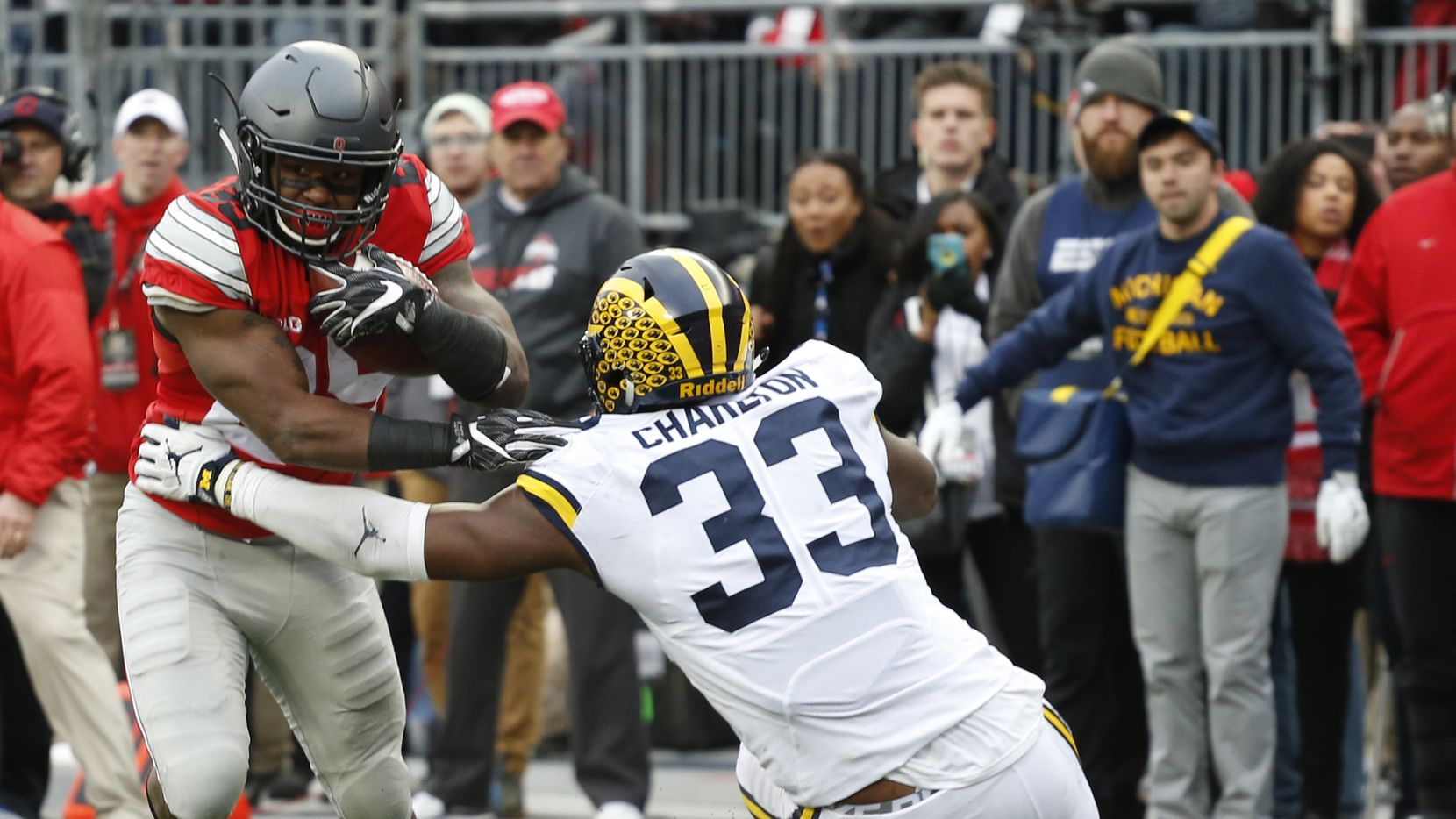 Ohio State running back Mike Weber, left, runs the ball as Michigan defensive end Taco Charlton makes the tackle during the second half of an NCAA college football game Saturday, Nov. 26, 2016, in Columbus, Ohio. Ohio State beat Michigan 30-27 in double overtime. (AP Photo/Jay LaPrete)