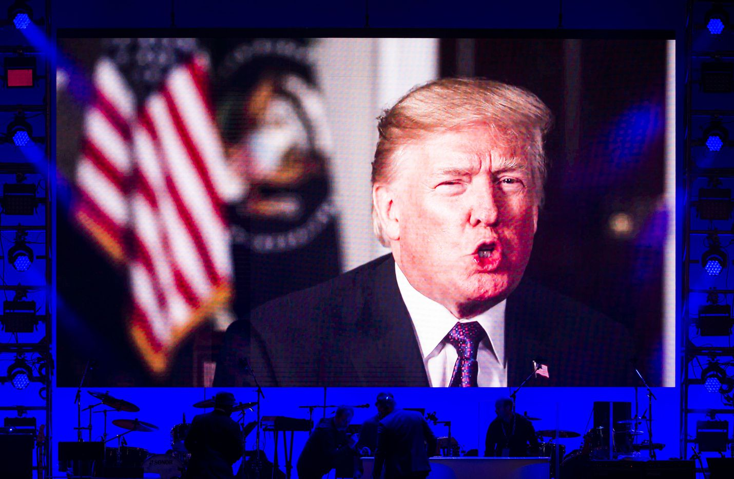 President Donald Trump speaks in a video message as stage hands set up between performers.