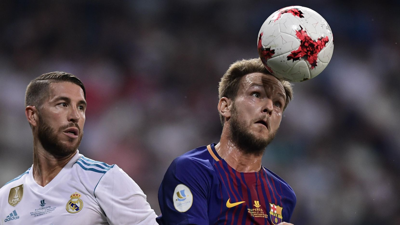 El mediocampista del Barcelona, el croata Ivan Rakitic (der.), cabecea el balón ante la presión del capitán del Madrid, Sergio Ramos, en el clásico español del 16 de agosto de 2017 en Madrid.(AFP/Getty Images)