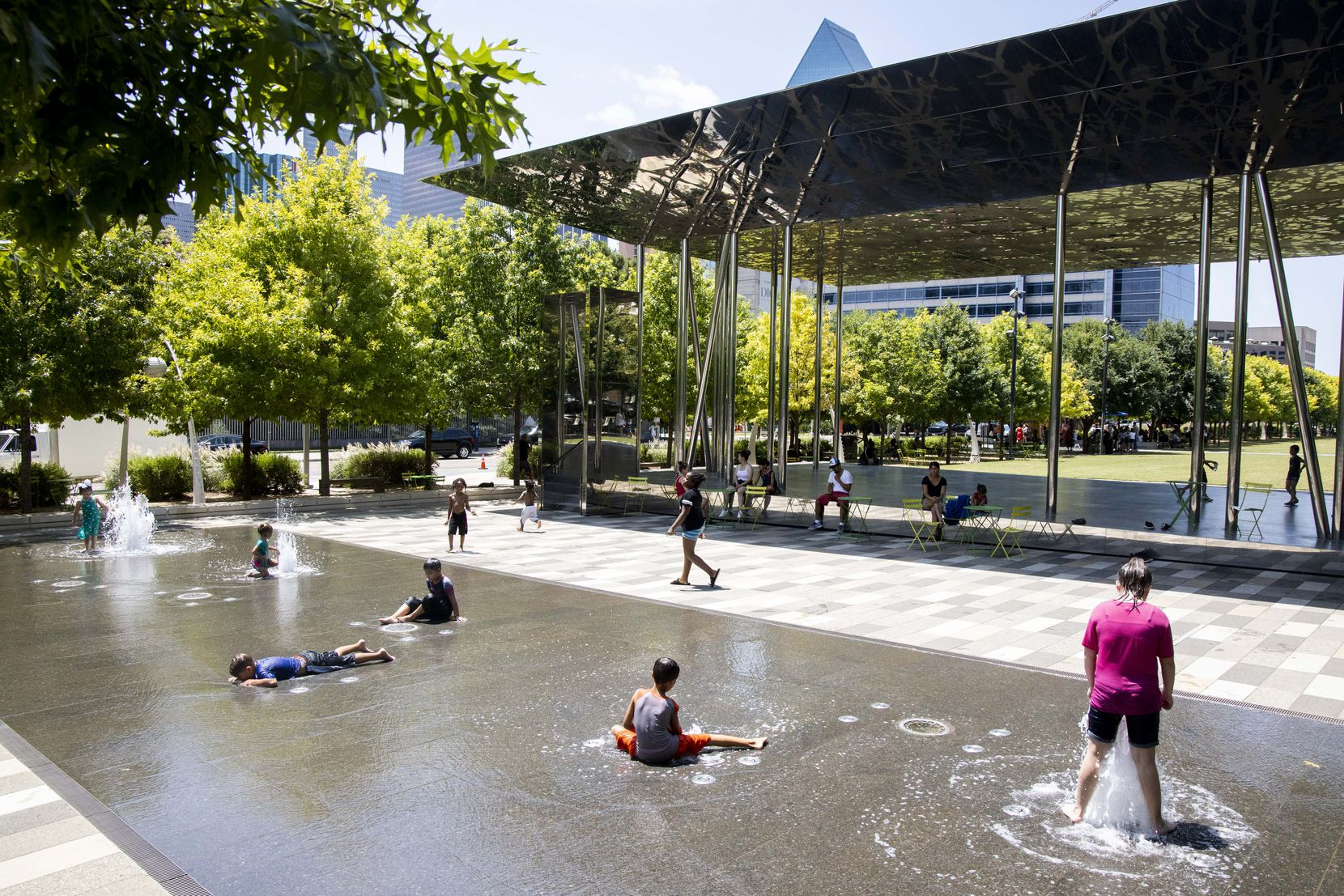 Kids cooled down in a water park at Klyde Warren Park on Tuesday. In Dallas-Fort Worth, an average summer high is about 94 degrees, according to the National Weather Service.