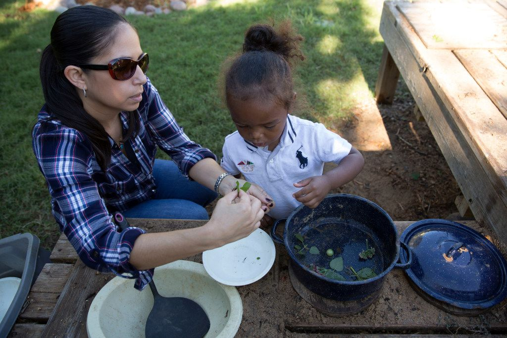Teacher Jamie Lenenberg works with Braylen Griffin, in the Vogel Alcove garden. The garden is used educationally in many  ways including patience.