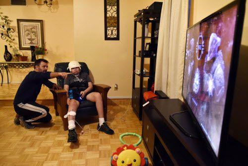 Andrés Gómez ayuda a su hijastro Esteban Monreal, 16, a jugar un videojuego en su casa en Arlington. Esteban fue atropellado mientras caminaba en la acera. Ben Torres/ Especial para Al Día