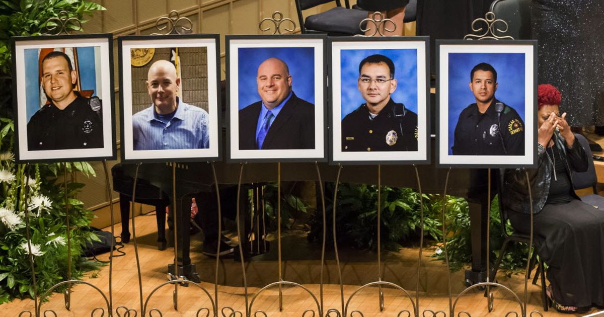 Photos of the fallen officers at a memorial service Tuesday in the Morton H. Meyerson Symphony Center.