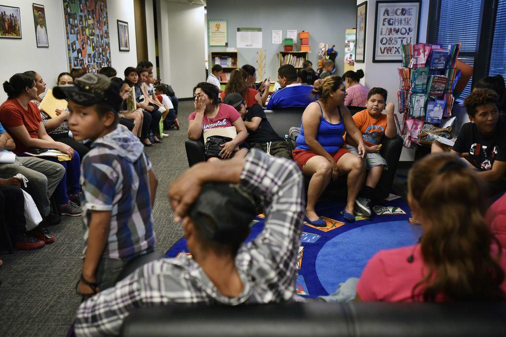 Decenas de familias recién llegadas esperaban para registrarse en el Intake Center del DISD el miércoles por la tarde.