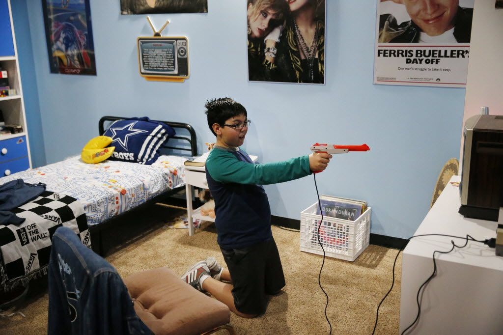 Frankie Valenzuela, 10, of Allen, plays a shooting game in a 1980s replica room during the soft opening of the National Videogame Museum at the Frisco Discovery Center in Frisco on March 26, 2016. (Andy Jacobsohn/The Dallas Morning News)
