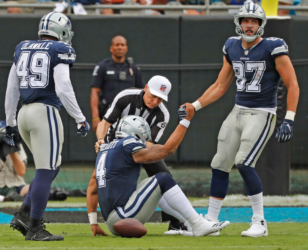Dallas Cowboys quarterback Dak Prescott (4) is helped to his feet by tight end Geoff Swaim (87) after being sacked in the second quarter during the Dallas Cowboys vs. the Carolina Panthers NFL football game at Bank of America Stadium in Charlotte, North Carolina on Sunday, September 9, 2018. (Louis DeLuca/The Dallas Morning News)