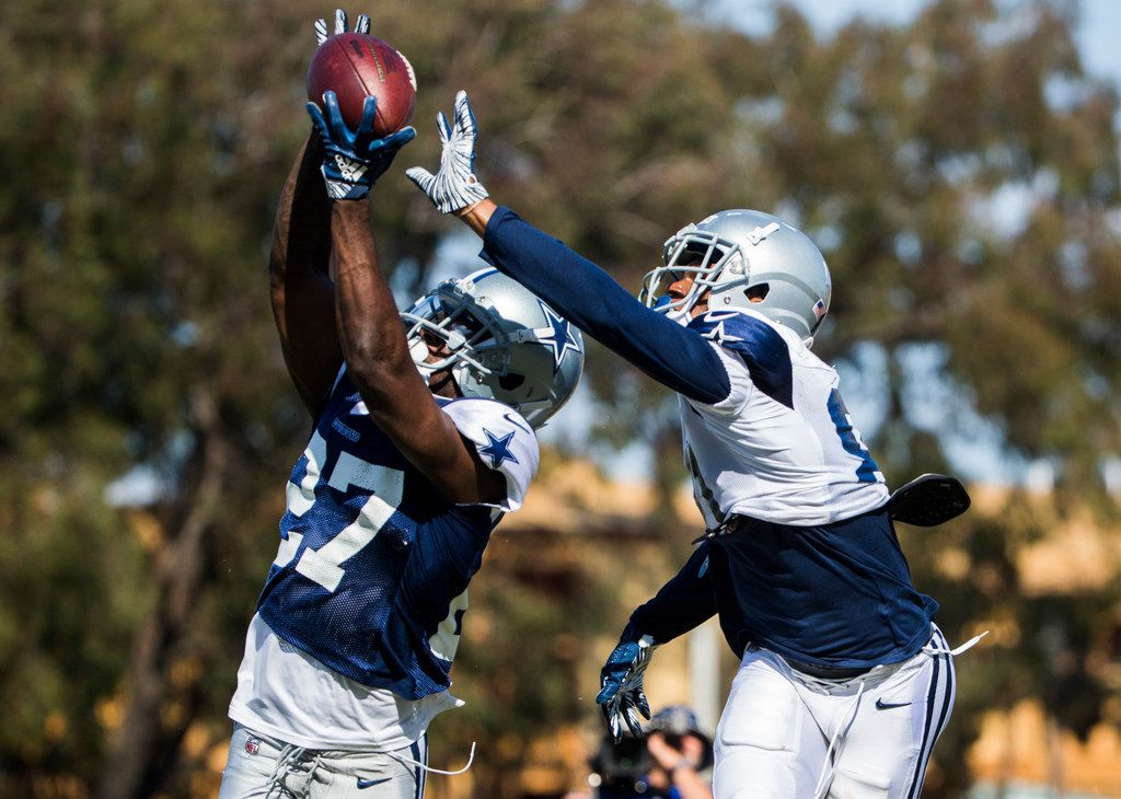 Dallas Cowboys cornerback Jourdan Lewis (27) intercepts a pass intended for wide receiver Jon'Vea Johnson (81) during an afternoon practice at training camp in Oxnard, California on Wednesday, August 7, 2019. (Ashley Landis/The Dallas Morning News)