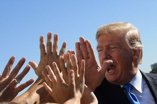 Donald Trump saluda a un grupo de estudiantes que fueron a recibirlo en el aeropuerto Dallas Love Field. GETTY IMAGES