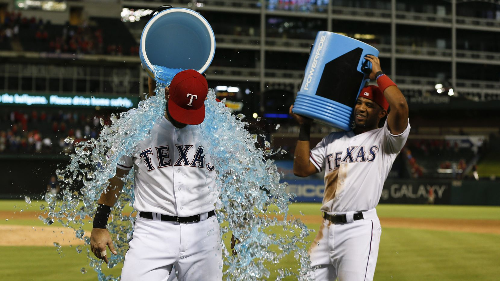 Sep 17, 2015; Arlington, TX, USA; Texas Rangers first baseman Mitch Moreland (18) is doused by teammates shortstop Elvis Andrus (1) and Rougned Odor following their teams win over the Houston Astros during a baseball game at Globe Life Park in Arlington. The Rangers won 8-2.