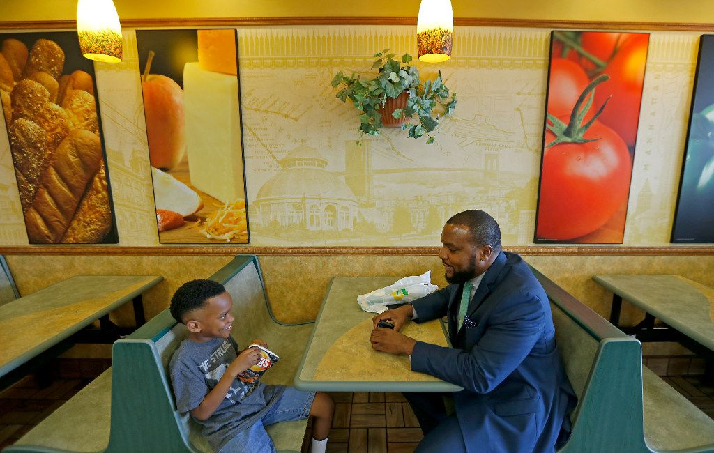 Attorney Lee Merritt (right) and his 7-year-old son Stacy Merritt, Jr., eat snacks and sandwiches at a Subway store in Allen.