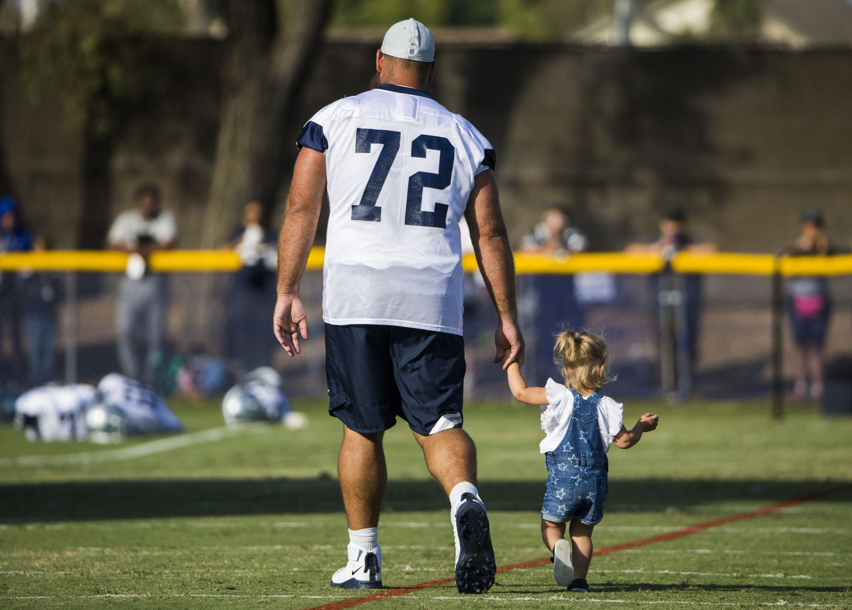 Dallas Cowboys center Travis Frederick (72) walks with his daughter after an afternoon practice at training camp in Oxnard, Calif., on July 29, 2019.