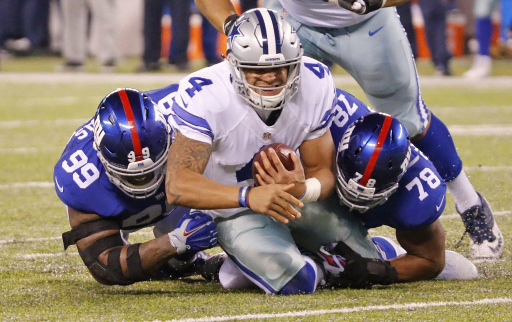 Dallas Cowboys quarterback Dak Prescott (4) is sacked by New York Giants nose tackle Robert Thomas (99) and defensive end Romeo Okwara (78) during the Dallas Cowboys vs. the New York Giants NFL football game at MetLife Stadium in East Rutherford, New Jersey on Sunday, December 11, 2016. (Louis DeLuca/The Dallas Morning News)