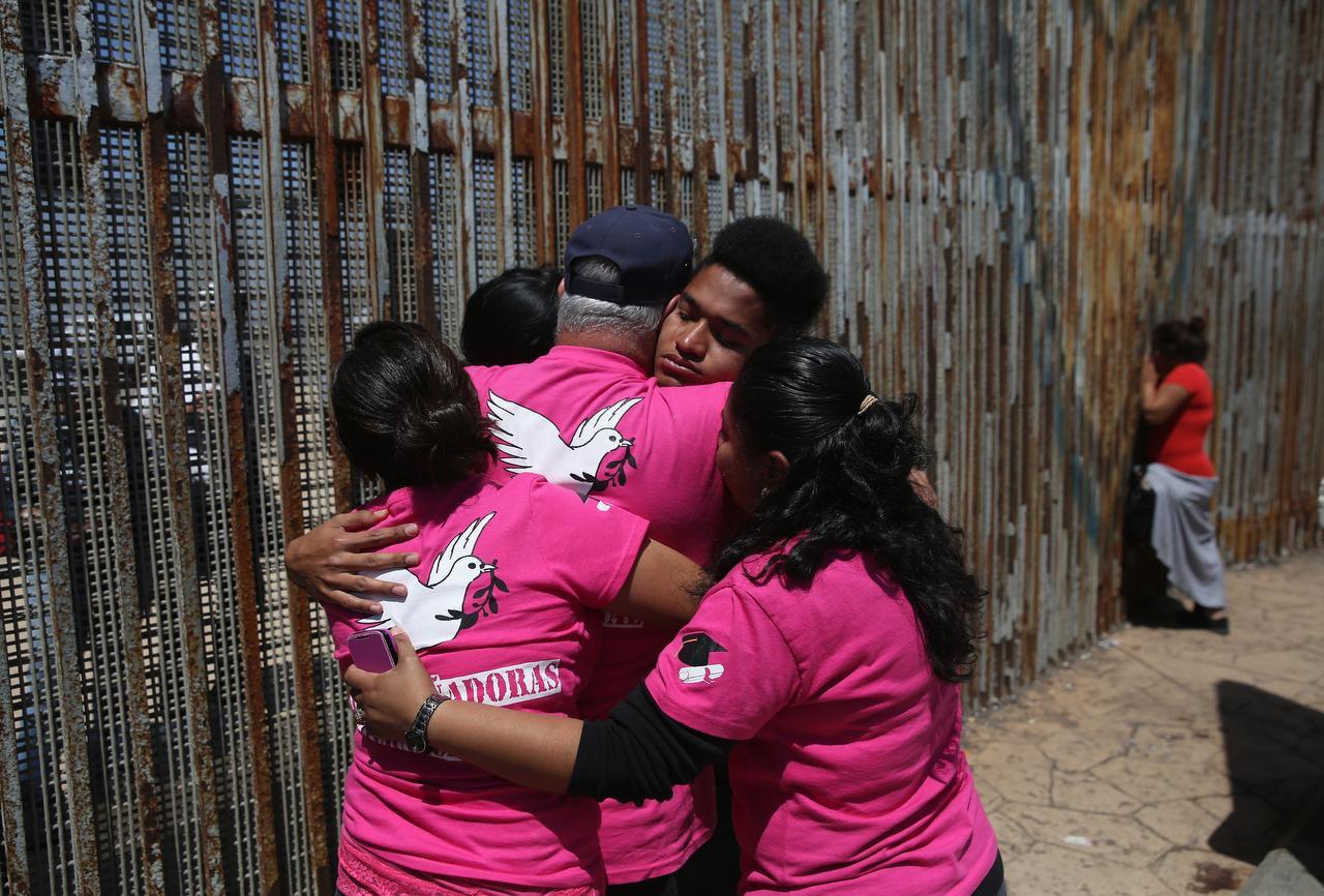 Familiares que fueron deportados y que tienen miembros que son 'dreamers' oran en la frontera entre México y Estados unidos, el 1 de mayo del 2016 en Tijuana, México. (GETTY IMAGES/JOHN MOORE)