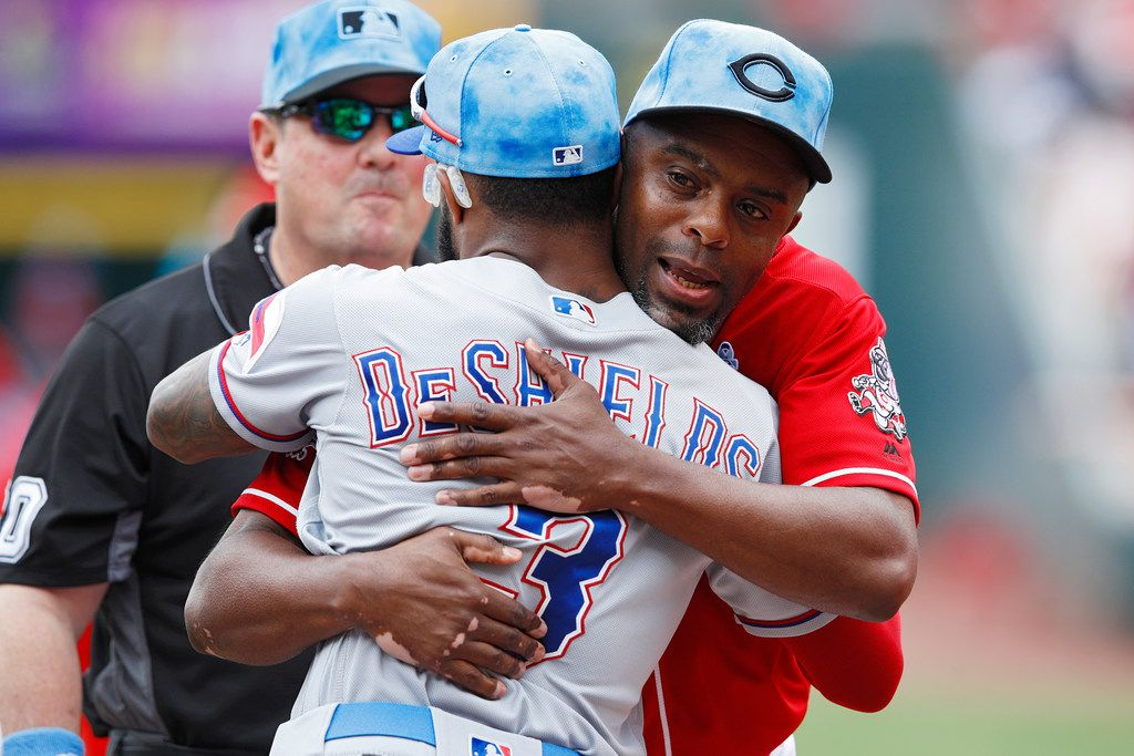CINCINNATI, OH - JUNE 16: First base coach Delino DeShields of the Cincinnati Reds hugs his son Delino DeShields Jr. #3 of the Texas Rangers as Father's Day is observed prior to a game at Great American Ball Park on June 16, 2019 in Cincinnati, Ohio. (Photo by Joe Robbins/Getty Images)