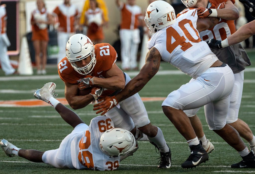 University of Texas running back Jordan Whittington (21) is tackled by defensive back Montrell Estell (39) as linebacker Ayodele Adeoye (40 ) reaches over to help during the Orange and White spring game held at Darrell K Royal-Texas Memorial Stadium on Saturday, April, 13, 2019, in Austin, Texas.  (Rodolfo Gonzalez/Special Contributor)