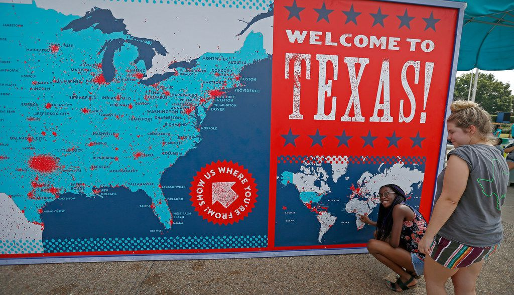 """Marina Dikosso (left), who is originally from Cameron, Africa, poses for a photograph with her friend Emily Estes after she puts a red dot sticker on the """"Where are you from?"""" board at the State Fair of Texas in Fair Park in Dallas in 2017."""