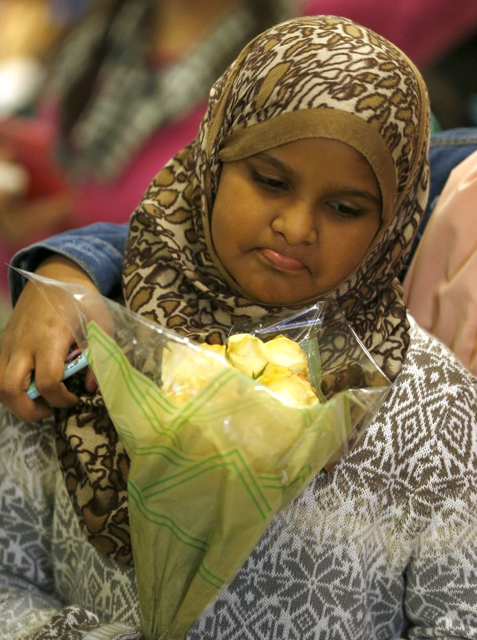 Muzen Elnur, 11, holds flowers while she waits for her grandmother from Sudan who was being detained at Dallas/Fort Worth International Airport in Dallas, Saturday, Jan. 28, 2017.