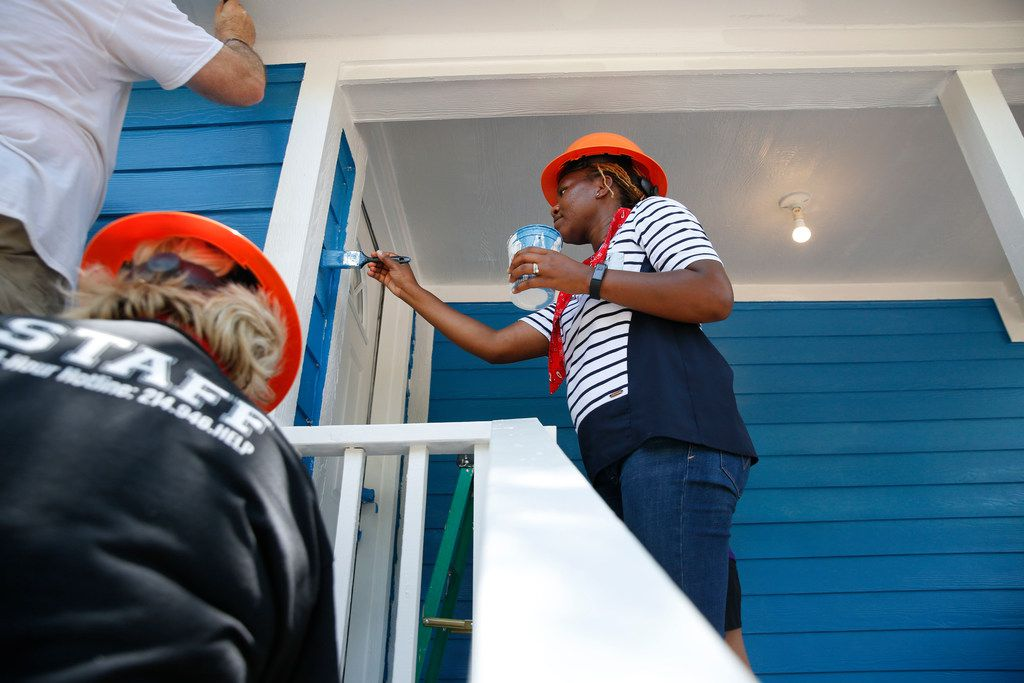 Chikwanda Chisanga, a volunteer from Child Protective Services, paints a home in West Dallas as part of the Dallas Area Habitat for Humanity on June 1, 2018.