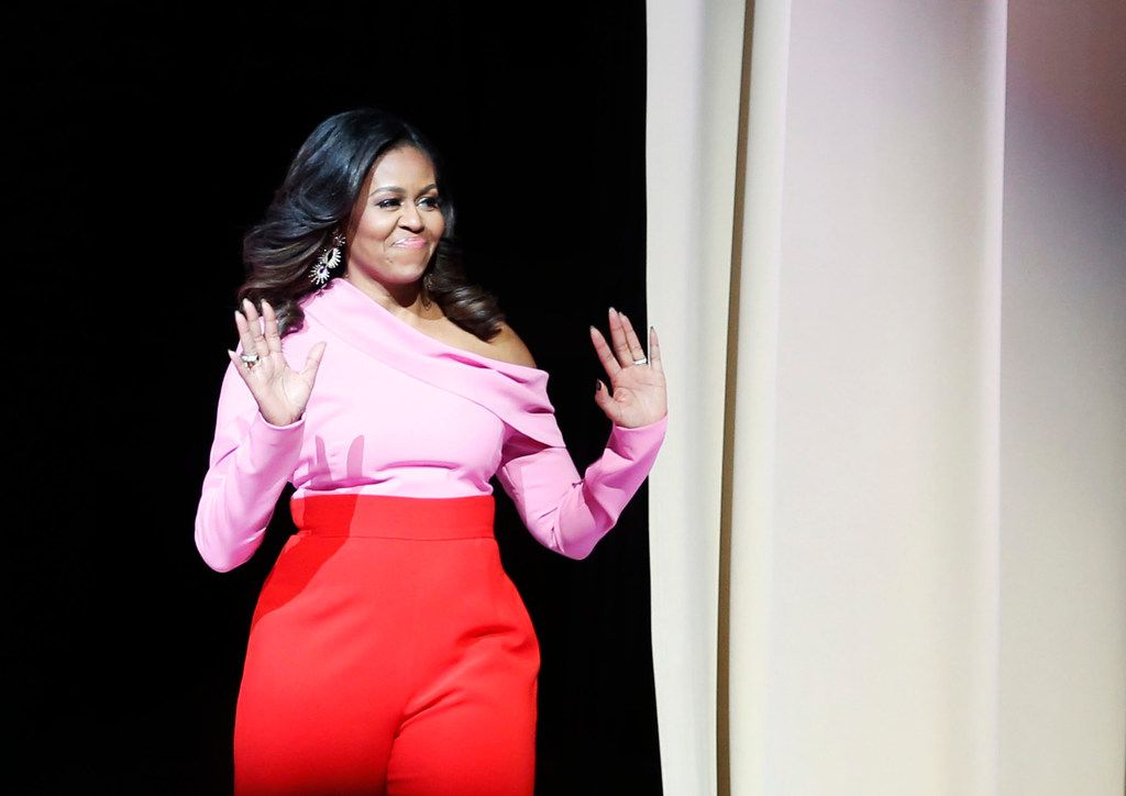 Former first lady Michelle Obama waved to the crowd as she made her way on the stage during an event promoting her book Becoming, at American Airlines Center in Dallas on Monday, December 17, 2018.