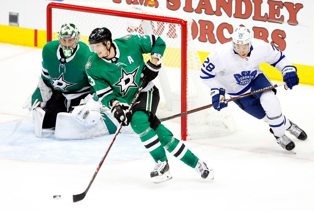 Dallas Stars defenseman John Klingberg (3) carries the puck up ice as he skates away from Toronto Maple Leafs right wing Connor Brown (28) during the third period at the American Airlines Center in Dallas, Tuesday, October 9, 2018. Tom Fox/The Dallas Morning News)