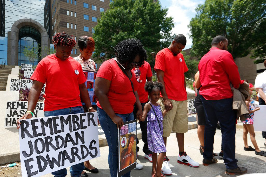 Jordan Edwards' family, including stepmother Charmaine Edwards (center), sister Korrie Edwards and father Odell Edwards, bowed their heads in prayer in front of the Frank Crowley Courts Building in May. (Ron Baselice/Staff Photographer)