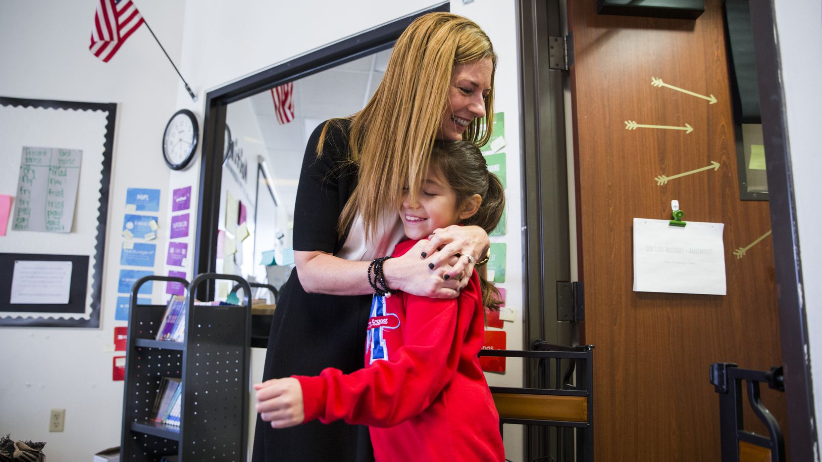Michelle Kinder, who is about to leave her job as executive director of the Momentous Institute, hugs fourth-grader Rebecca before morning circle time last week.