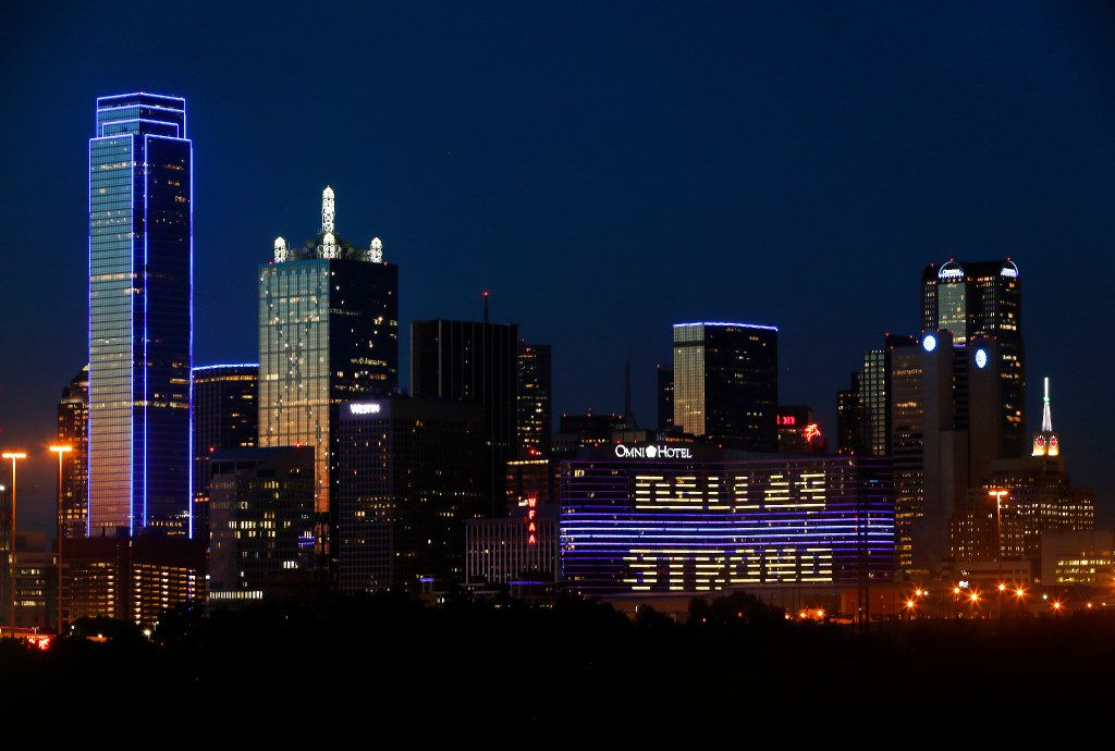 "The Omni Dallas Hotel (right) reads ""Dallas Strong"" as the skyline of Dallas is aglow in blue, Friday, July 7, 2017 to remember the four Dallas police officers and one DART (Dallas Area Rapid Transit) officer killed a year ago today in the 7/7/16 ambush attack on police. (Tom Fox/The Dallas Morning News)"