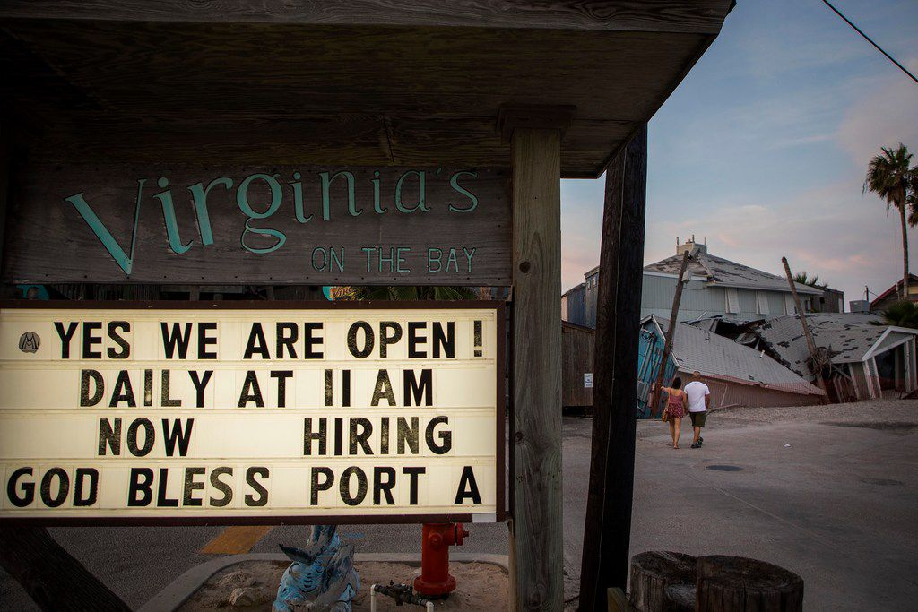 A sign at Virginia's On The Bay restaurant n Port Aransas advertises that the restaurant is open and hiring as a couple, who identified themselves only as Jesse and Stacy from San Antonio, check out remains of the former Pelican Club, still in ruins nearly a year after Hurricane Harvey.