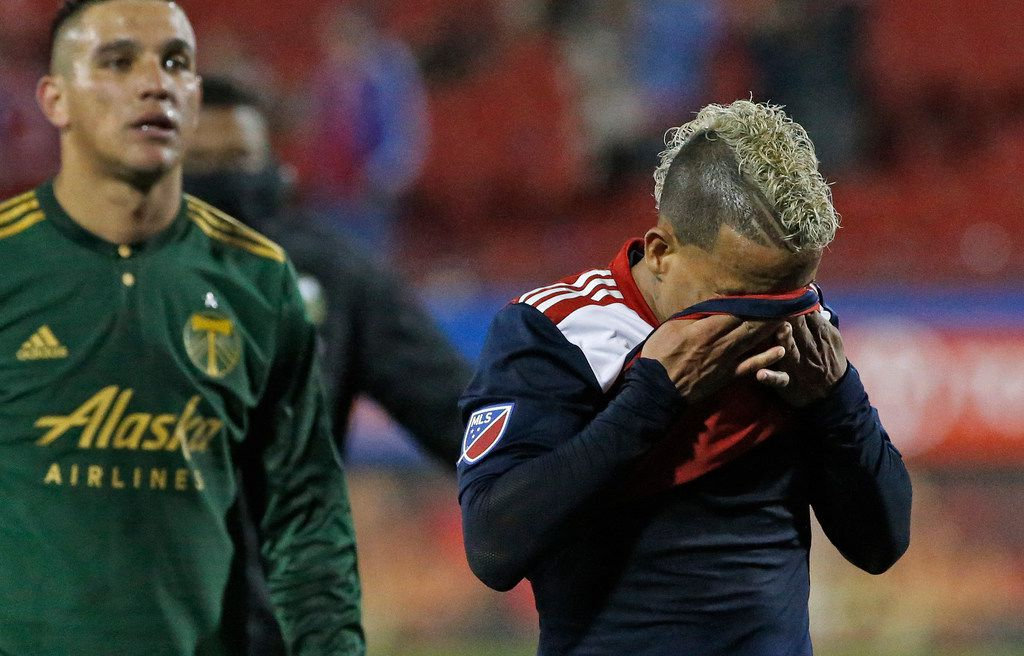 FC Dallas midfielder Michael Barrios (21) reacts emotionally as he heads to the locker room after FC Dallas' season-ending 2-1 loss, as Portland Timbers midfielder David Guzman (20) walks alongside after the FC Dallas vs. the Portland Timbers playoff soccer game at Toyota Stadium in Frisco, Texas on Wednesday, October 31, 2018. (Louis DeLuca/The Dallas Morning News)