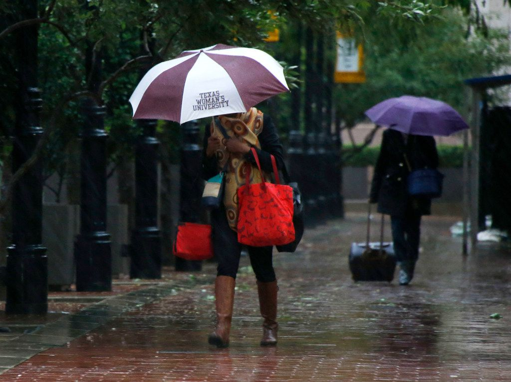 People make their way through wet and cold conditions as temperatures dropped into the 40's in downtown Dallas on Monday, October 15, 2018.