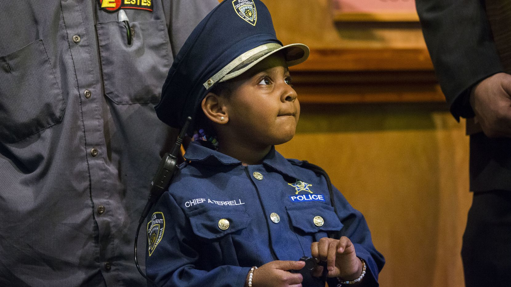 """Four-year-old Ah'Maya Terrell stands in front of her grandfather Derek Hollands as she is designated as the Cedar Hill Police Department's  """"chief for a day"""" during a City Council meeting in Cedar Hill on March 26, 2019."""
