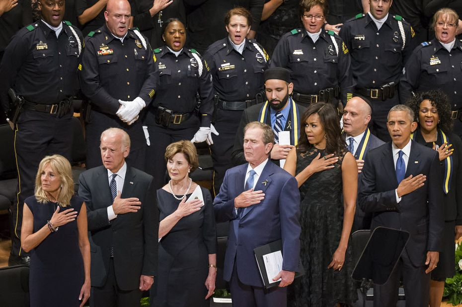 From left, Jill Biden, Vice President  Joe Biden, Laura Bush, former President George W. Bush, Michelle Obama and President Barack Obama stand for the national anthem during an interfaith memorial service at the Morton H. Meyerson Symphony Center in Dallas on Tuesday, July 12, 2016, for five law enforcement officers killed in an ambush at a Black Lives Matter rally.