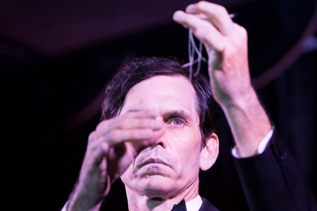 Magician Zabrecky performs a magic trick on stage at the Peacock Theater.