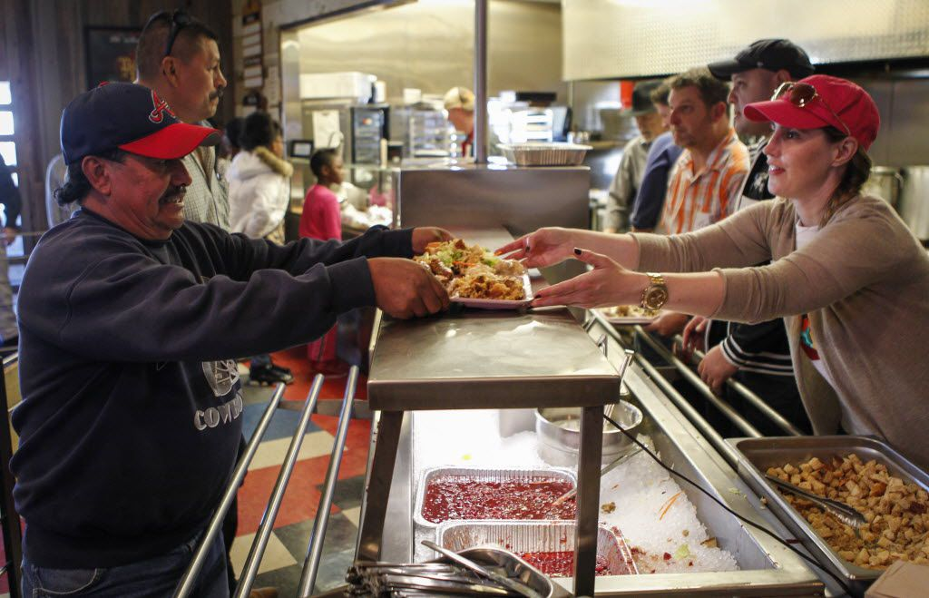 Volunteer Tanya Ragan , right, serves a free Thanksgiving Day meal to Pablo Guzman, left, of West Dallas at The Slow Bone in the Design District of Dallas on Thursday, Nov. 27, 2014. Here's a list of the places to find free Thanksgiving dinner in 2016 in Dallas and Fort Worth.