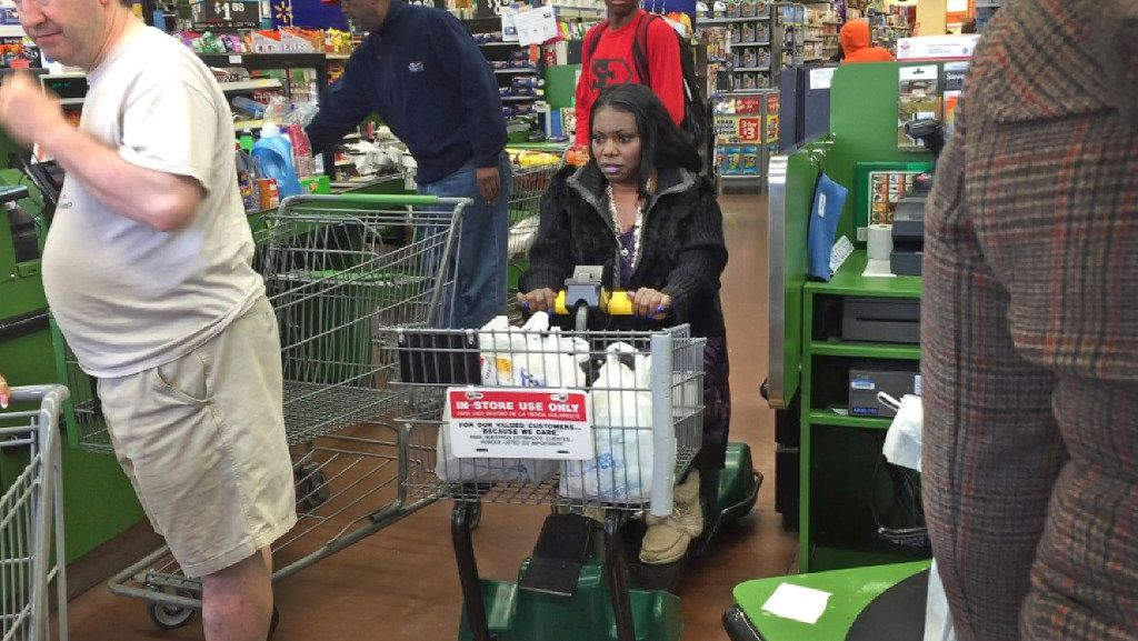 Mythia Joseph navigates the checkout area on a motorized scooter at the Wal-Mart near Hall Street and Central Expressway near her Roseland Estates home. (Louis DeLuca/Staff Photographer)