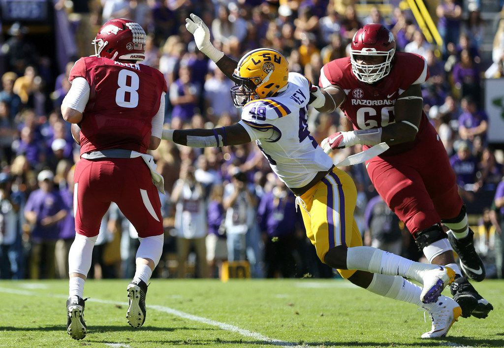 FILE - In this Nov. 11, 2017, file photo, Arkansas quarterback Austin Allen (8) scrambles under pressure from LSU linebacker Arden Key (49) in the first half of an NCAA college football game, in Baton Rouge, La. Arden Key was selected to the AP All-Conference SEC team announced Monday, Dec. 4, 2017. (AP Photo/Gerald Herbert, File)