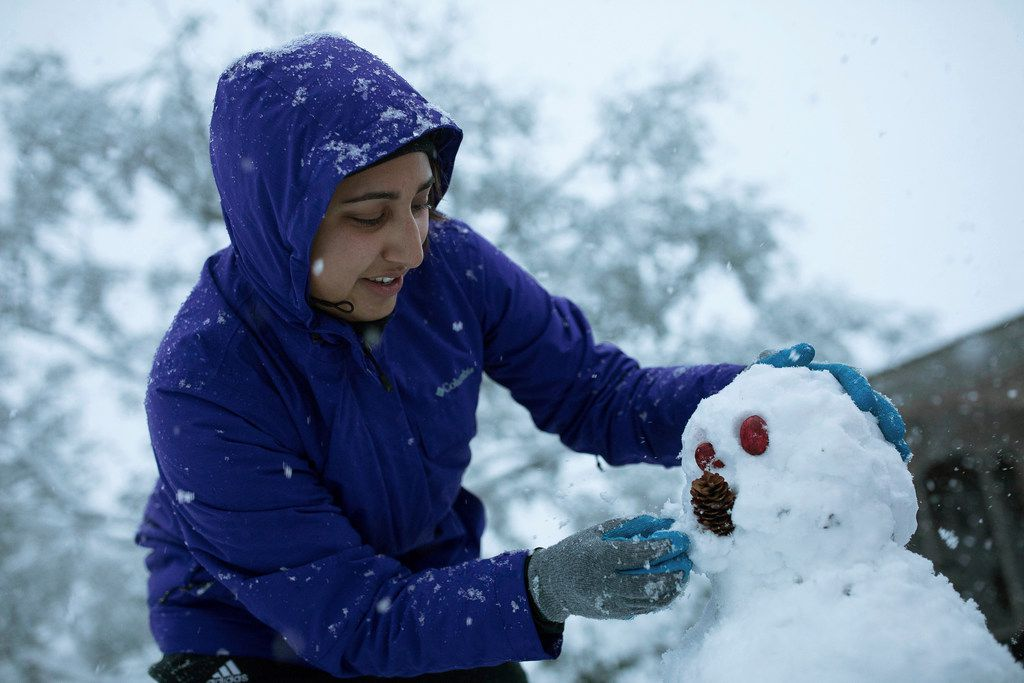 Megan Olivarez makes her first snow man in front of her home in Corpus Christi, Texas, following a night of snow on Friday, Dec. 8, 2017.