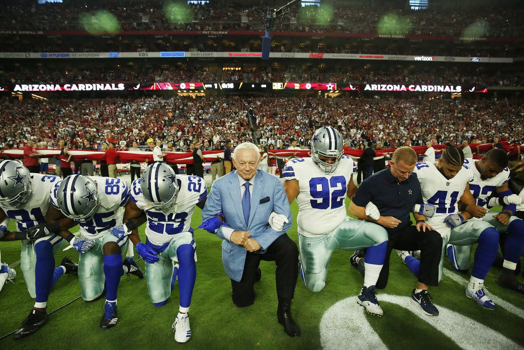 Dallas Cowboys free safety Byron Jones (31), wide receiver Noah Brown (85), defensive back Bene' Benwikere (23), owner Jerry Jones, defensive tackle Brian Price (92), head coach Jason Garrett and fullback Keith Smith (41) take a knee with teammates before the playing of the United States National Anthem before a National Football League game between the Dallas Cowboys and the Arizona Cardinals at University of Phoenix Stadium in Glendale, Arizona on Monday September 25, 2017. (Andy Jacobsohn/The Dallas Morning News)