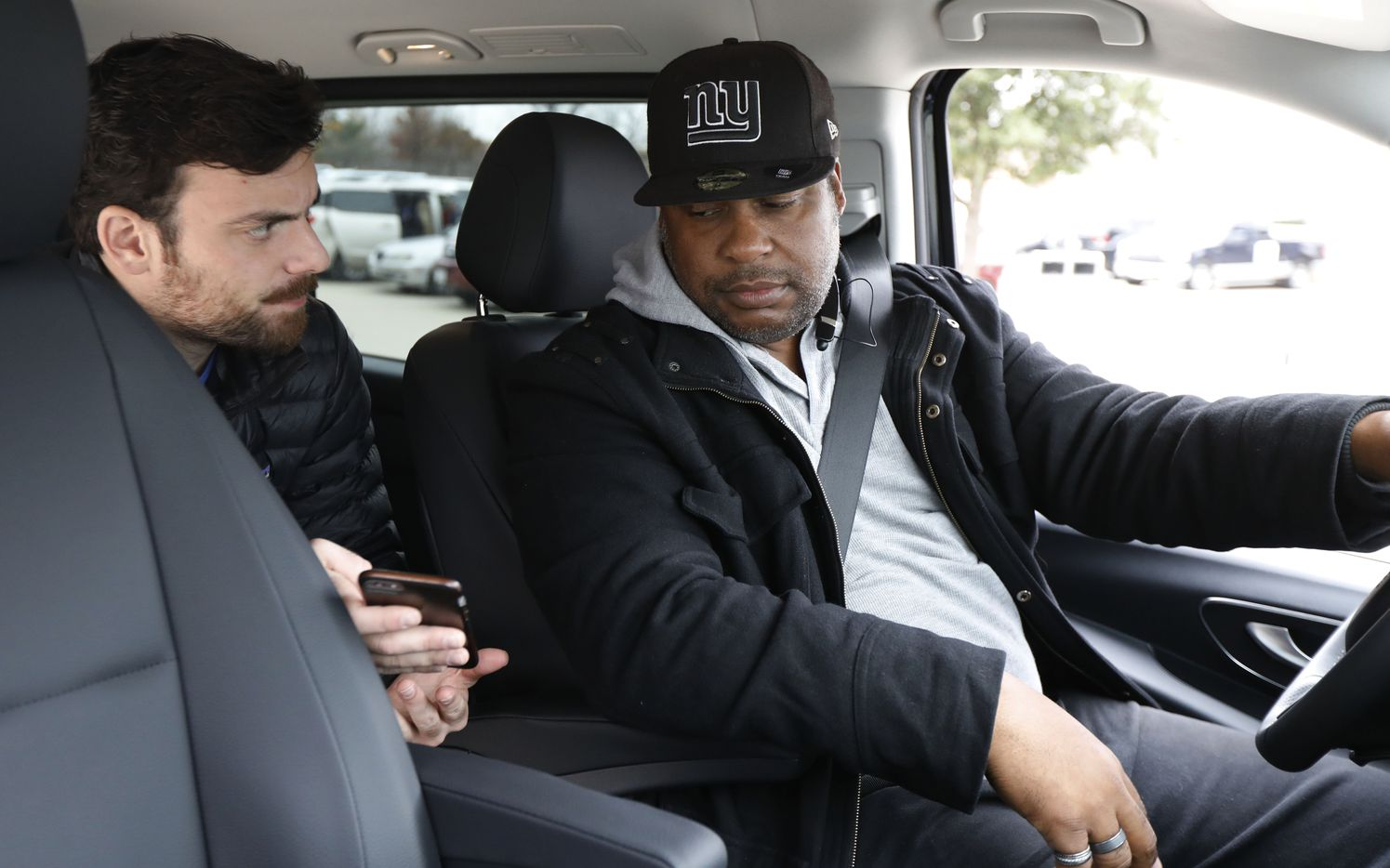 Brendan Meyer checks his app with Miles Williams, a driver for Via, at the TRE CentrePort/DFW Airport station in Fort Worth. Via would take him to AT&T Stadium in Arlington.
