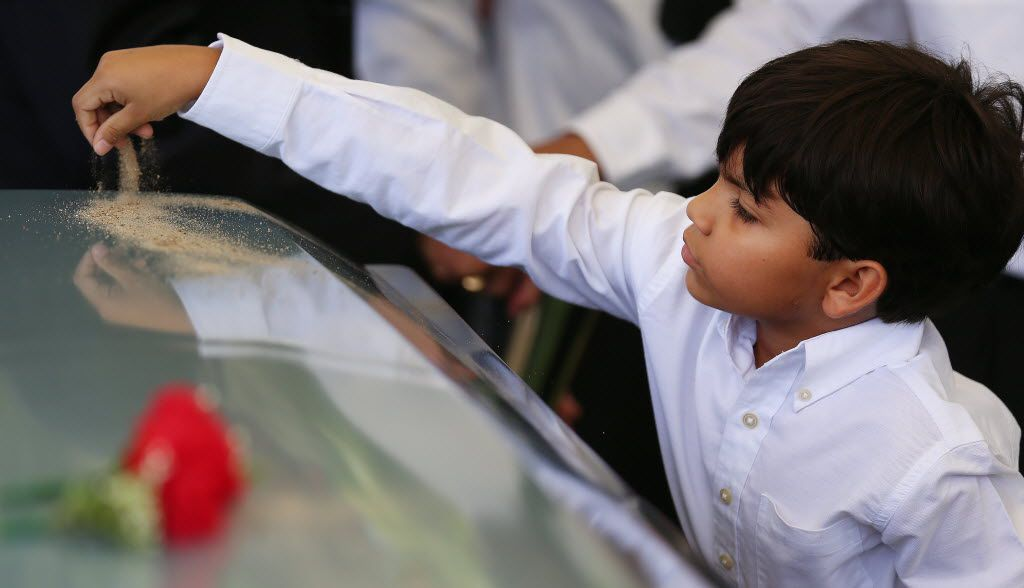 Eight-year-old Nicholas Garcia placed dirt on the casket of his grandfather Felix Lozada at the burial ceremony in Dallas.